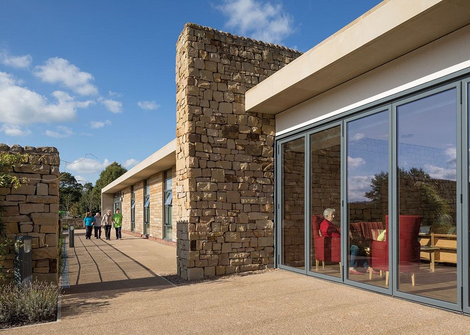 Local stone is used both as ashlar and, as here, referencing the drystone walls of the area.