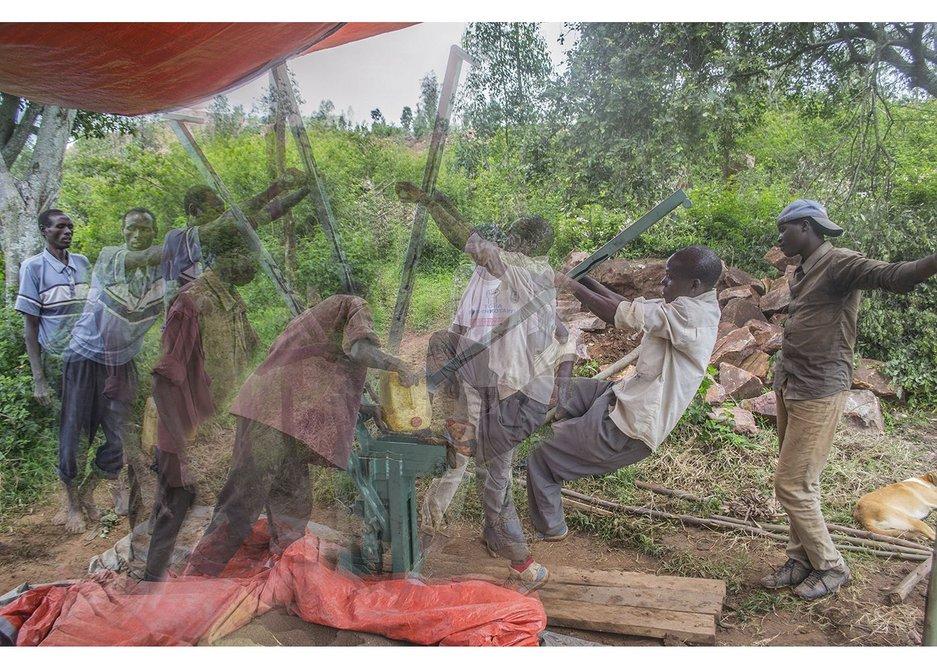 Jean Bosco compacts one earth block with the Makiga block machine, Ntarama, Rwanda, November 2014.
