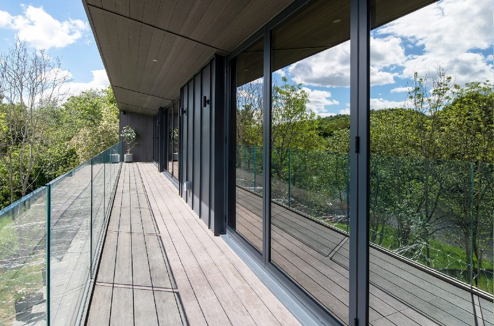 The covered first-floor terrace lined with Schüco sliding doors.