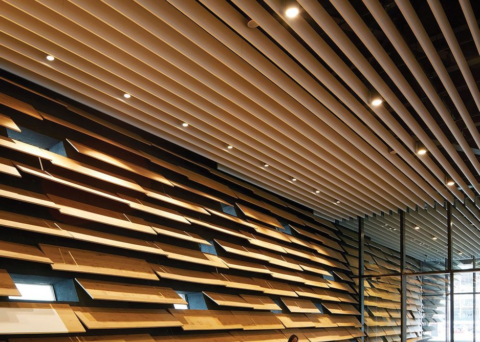 The slats of the exterior cladding recur internally in timber.
