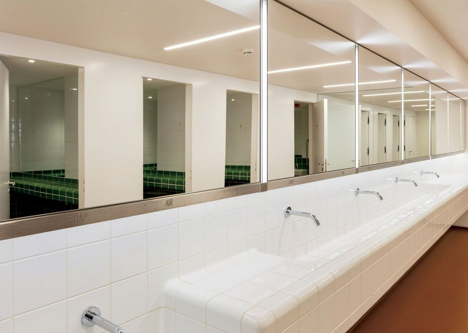WC walls and sink trough are clad in curved green and white Dutch tiles.