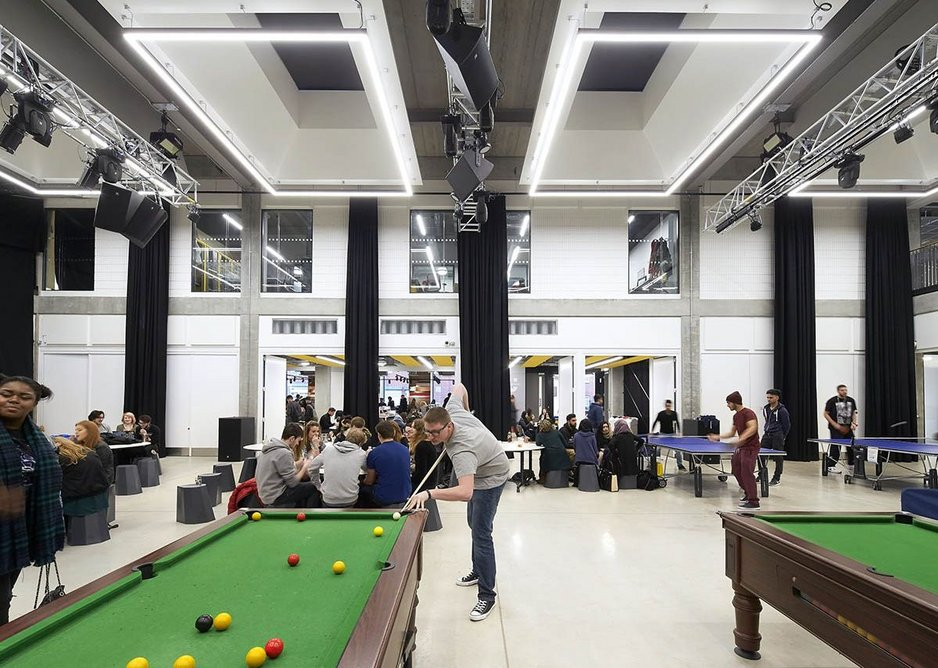 The union hall as play zone, games, white walls, rooflights open.