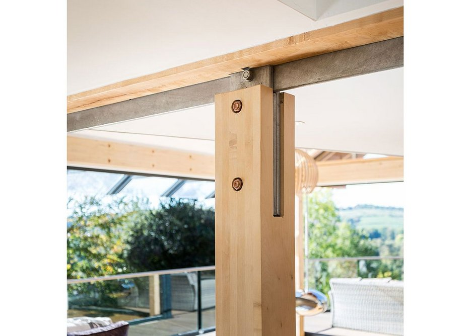 Steel reinforced junction of laminated sycamore structural beams and columns.