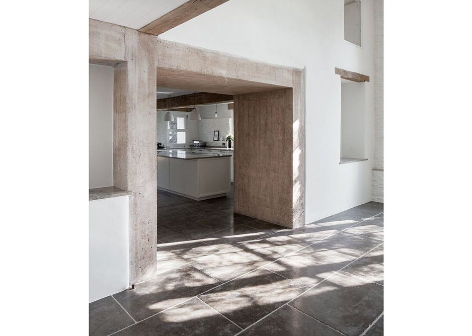 Broad beams of air-dried oak work with a board mark concrete portal to supporting new openings in the house. Lintels are left exposed.