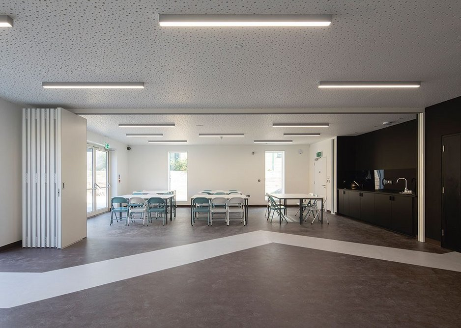 The community space can be divided into two by concertina partition walls. Each part has its own kitchenette and access to the garden.