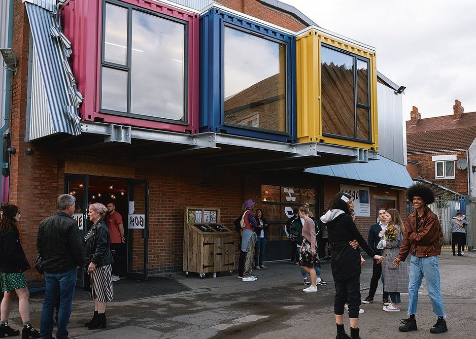 Shipping containers punched through the facade enliven the street.