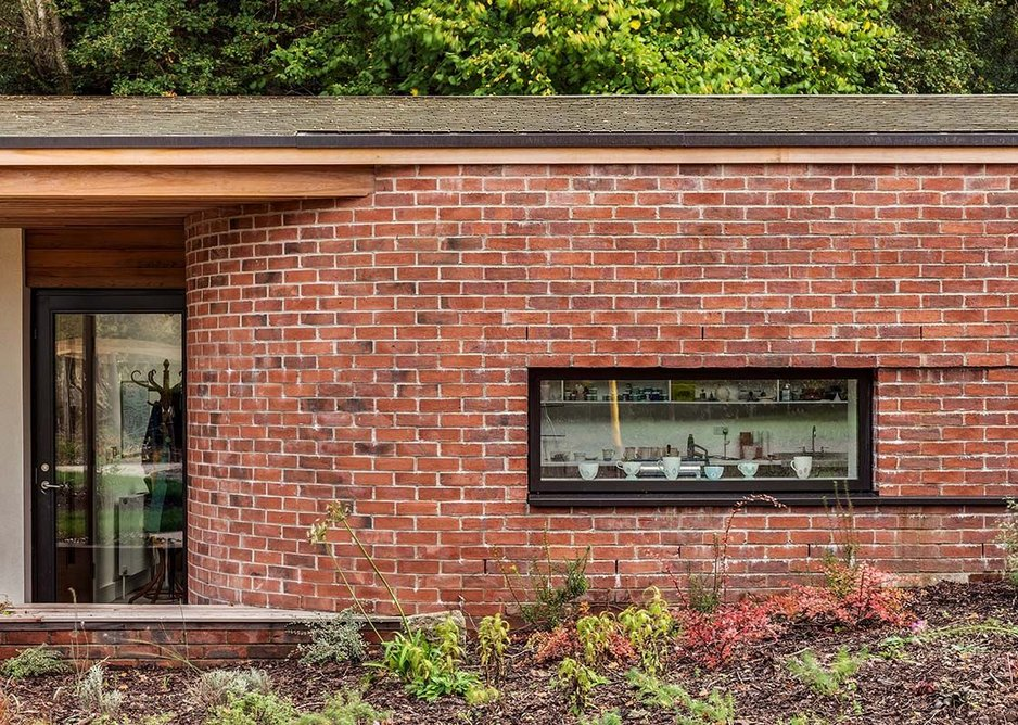 Bricks curve to create an inviting entrance. Companion's pottery is on display in the windows.