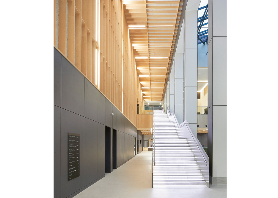 The grand connecting staircase runs up the atrium alongside the service spine.