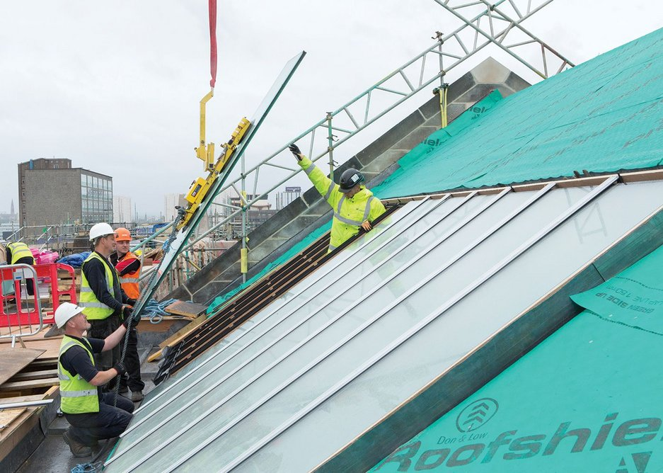 Installing the glass on one of the rooftop studios.