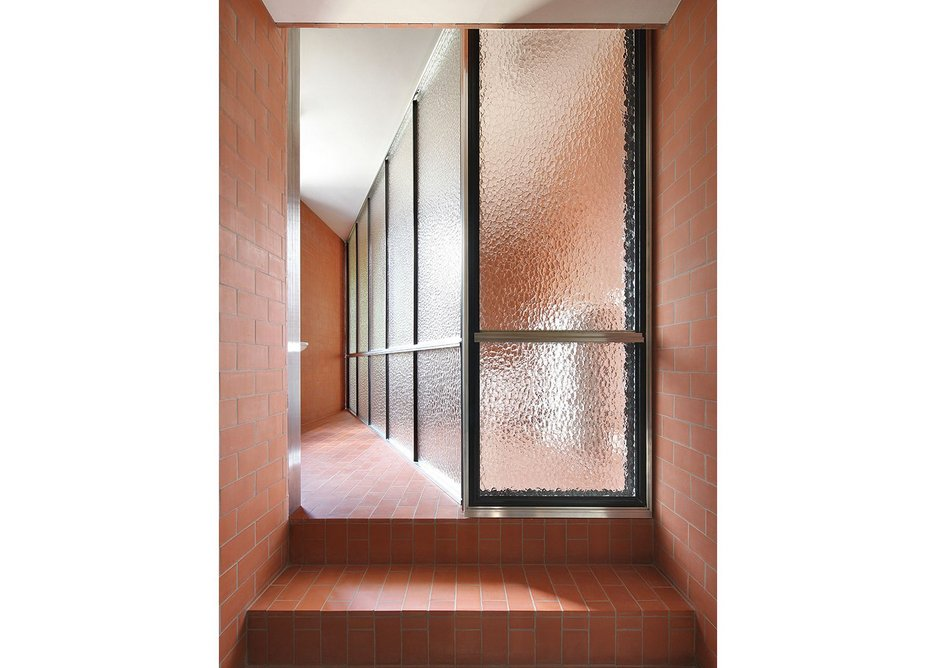 The simple brick ablution area has been split into four distinct spaces using framed mottled glass.