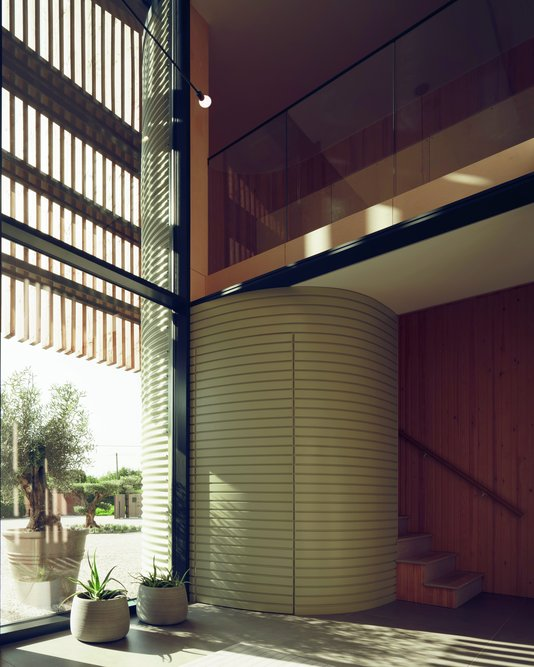 Green corrugated metal cladding on the elevation follows through around the stairwell in painted timber.