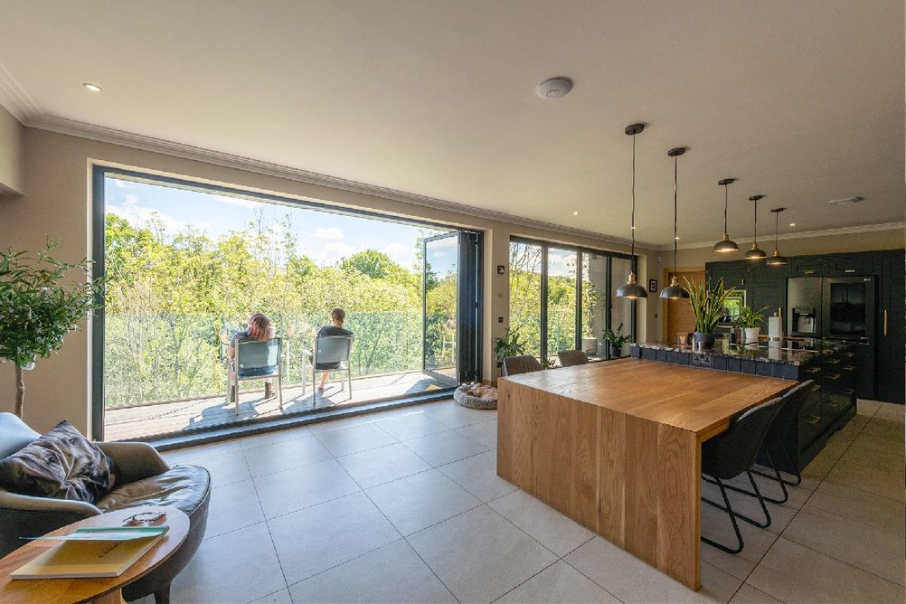 The first-floor kitchen dining space with balcony, glass balustrade and Schüco bi-fold doors.
