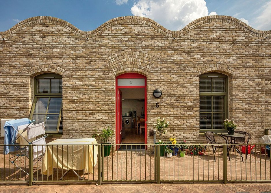 Homes have individually coloured front doors, and the wavy roofline echoes vaulted ceilings inside.