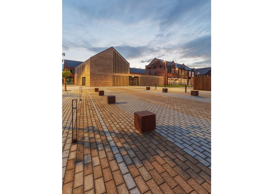 A new small civic square leads to the stone-clad combined entrance to the care centre library and public café. Credit Glancy Nicholls Architects