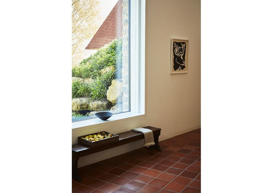 The unfussy interior has a simple materials palette including ceramic floor tiles and white walls.