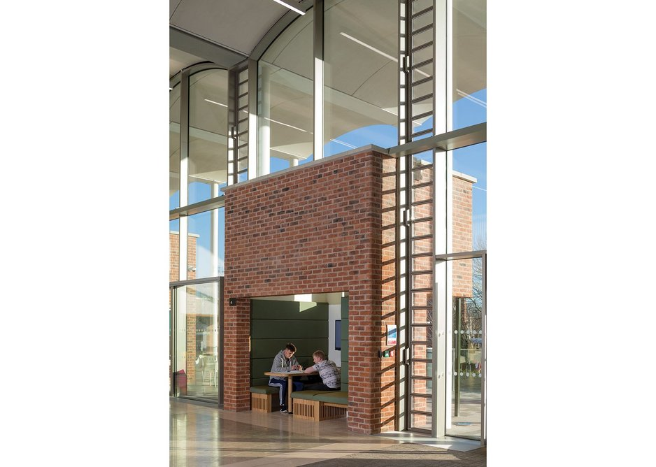 Brick cubes mediate between interior and colonnade, containing semi-private study spaces.