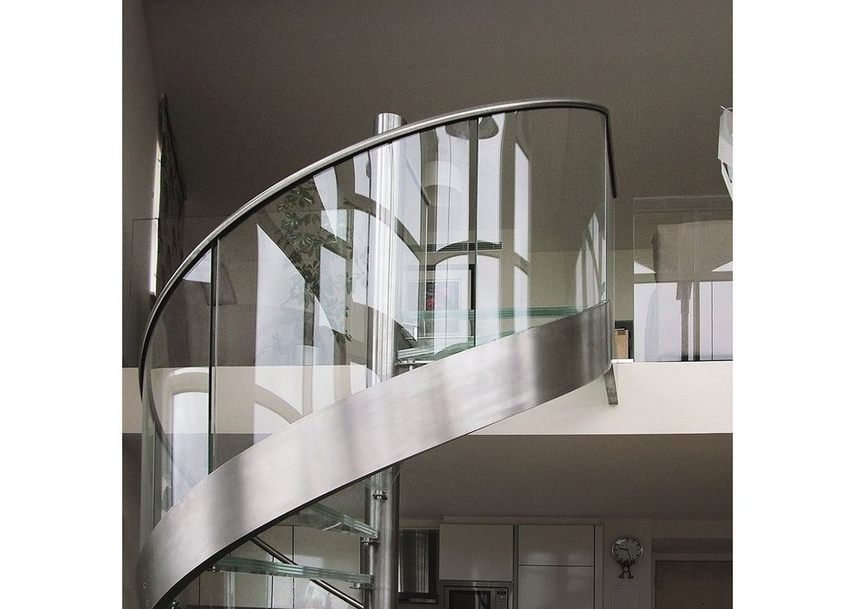 A sweeping Canal Engineering stair with glass treads and a curving glass balustrade