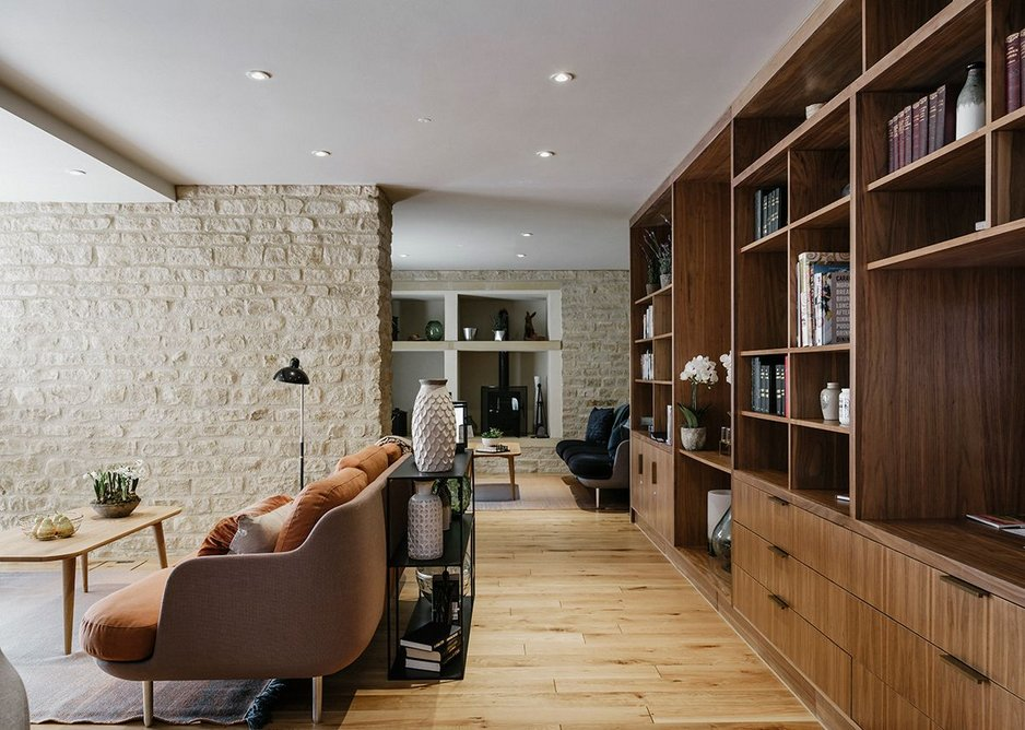 The residents lounge is gently divided into rooms by stone clad fin walls .
