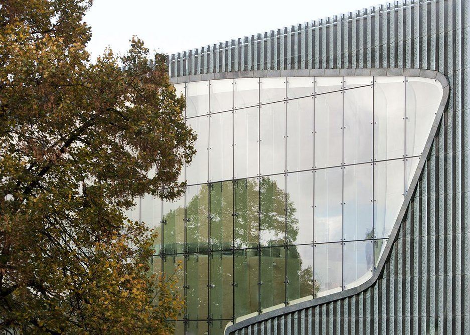 The building is defined by austere, orthogonal glass and copper mesh facades.