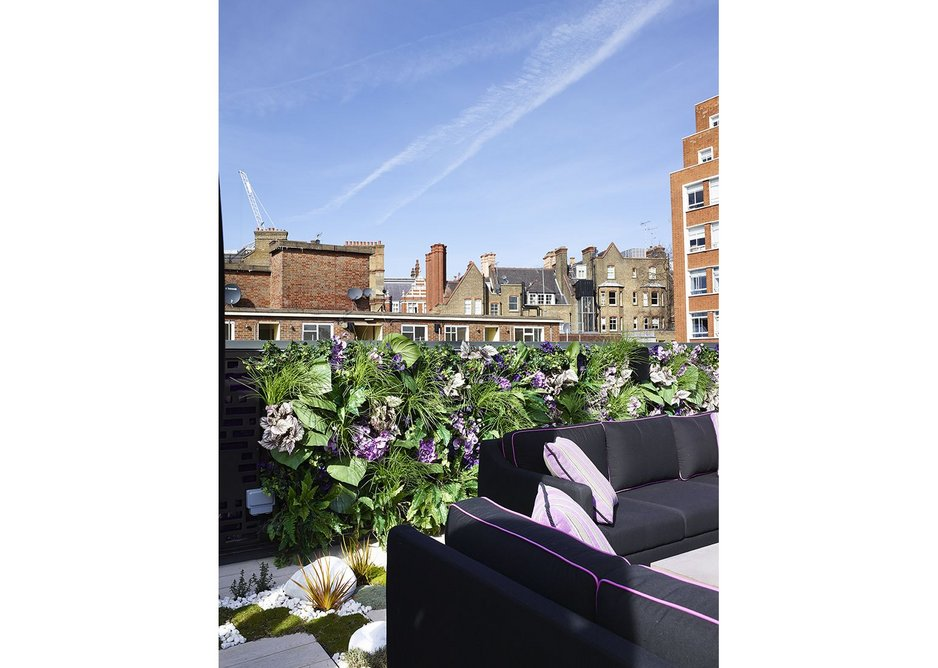 The extensive roof terrace is recessed between two pitched roofs, creating a large but unobtrusive entertaining and dining space
