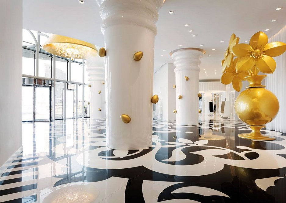 Laser-cut black and white tiles create a supersize pattern for the larger-than-life entrance lobby.