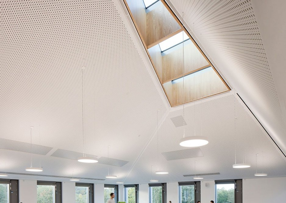 Built-in furniture mirrors the triangular rooflights above.