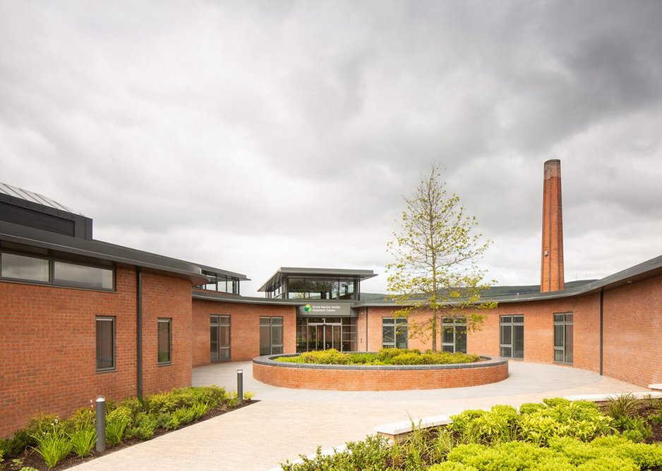 The point of arrival is the first of a sequence of landscaped courts. Chimney of existing building to the rear.
