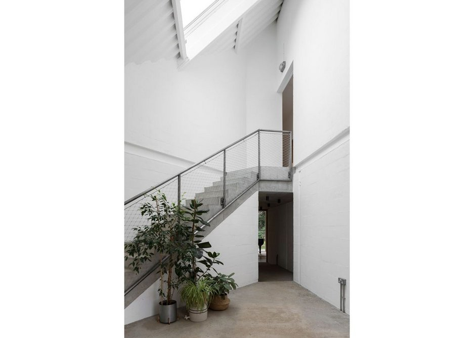 The full height entrance atrium with its concrete stair set at 45º across the plan.