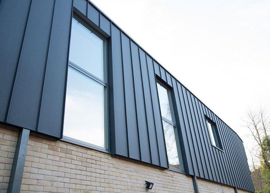 Dark grey external aluminium complements Ecclestoun's seamed aluminium roof.