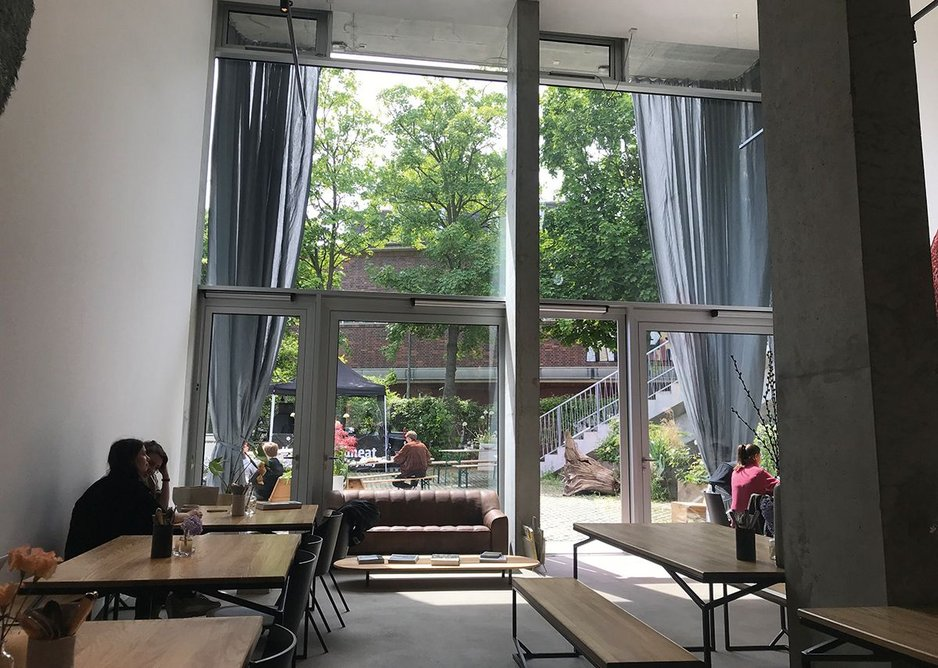 The ground floor double-height spaces provide community/commercial units; here a café.