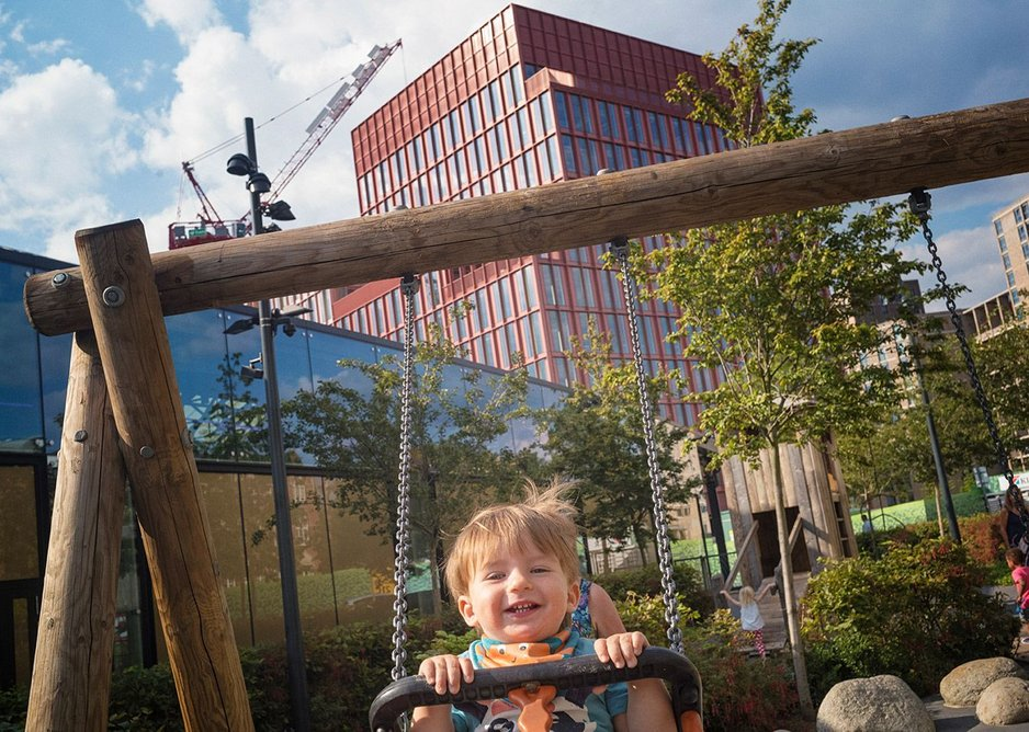 """Happy in the adventure playground, with the Duggan Morris """"Pink Building"""" behind."""