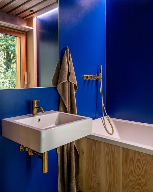 The Yves Klein blue continues in the bathroom, over the walls with tadelakt-style plaster and complementary gold faucets.