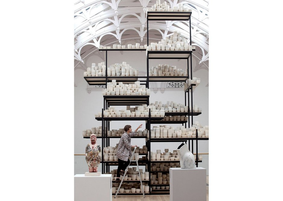 Artist Clare Twomey carefully balancing the 10,000 pots.