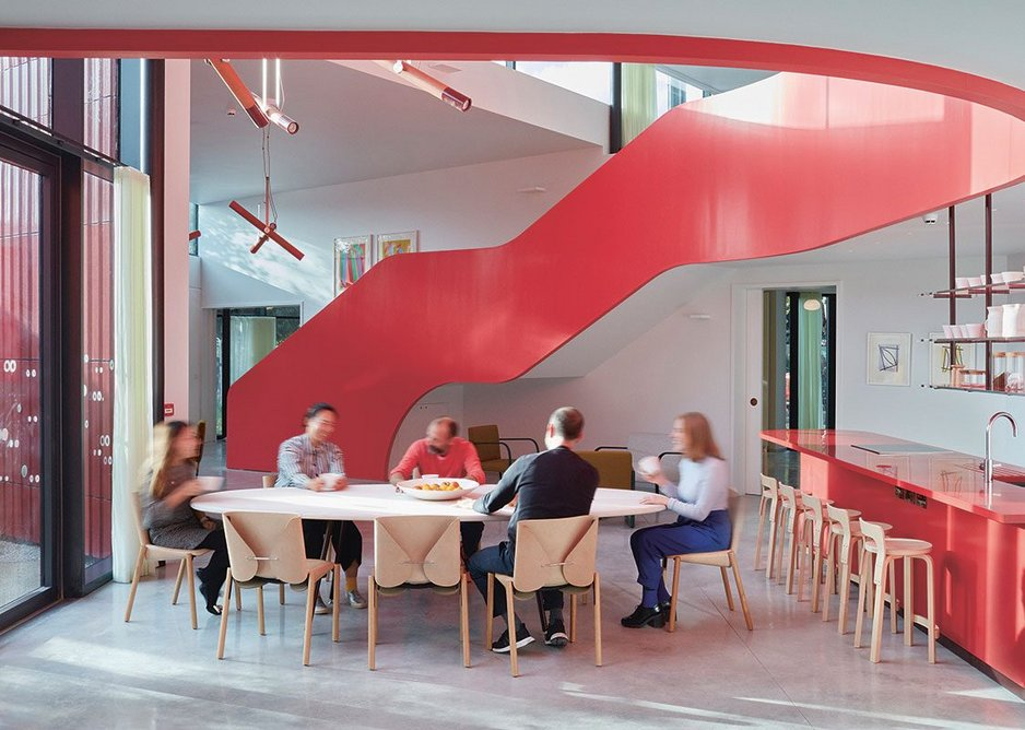 The red, wrapping staircase and cooking area identify the kitchen as the centre's nucleus.