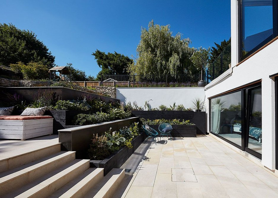 The house is half sunk below ground level, with bedrooms at basement level and a planted staggered garden around it.