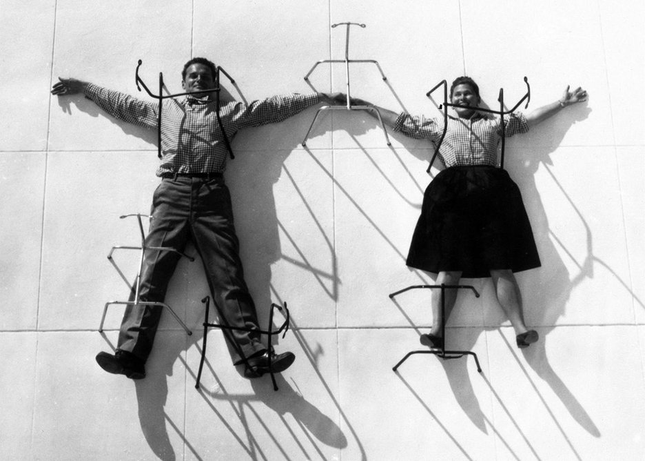 Charles and Ray Eames posing with chair bases.