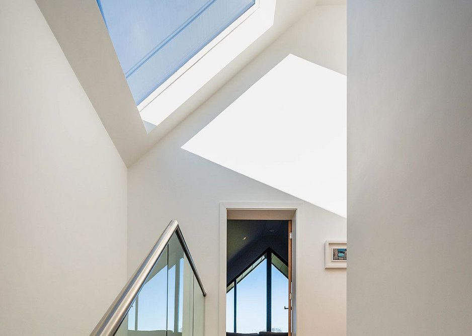 A frameless roof window floods the hall with light and provides open skyscape views.