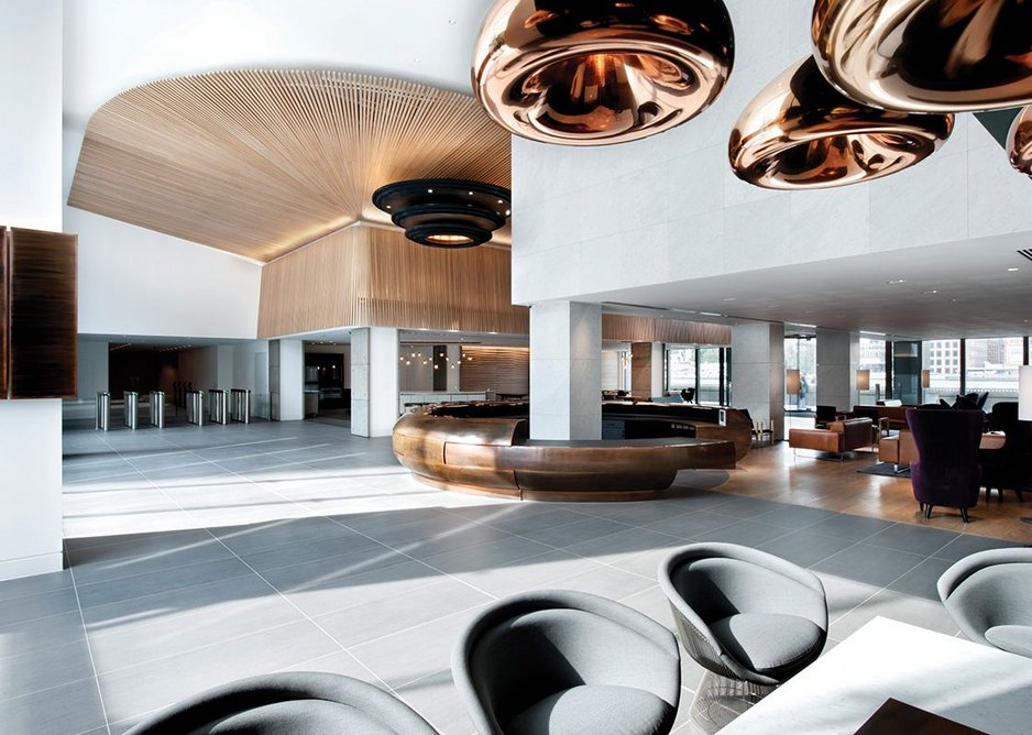 Tom Dixon-designed brass pendant lights hang in the brightly-lit lobby.