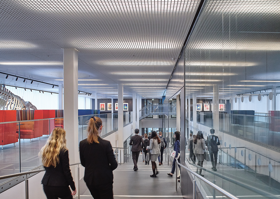 View down the stepped ramp, wheelchair inaccessible classrooms on the right, breakout spaces and seaside stripe sofas on the left.