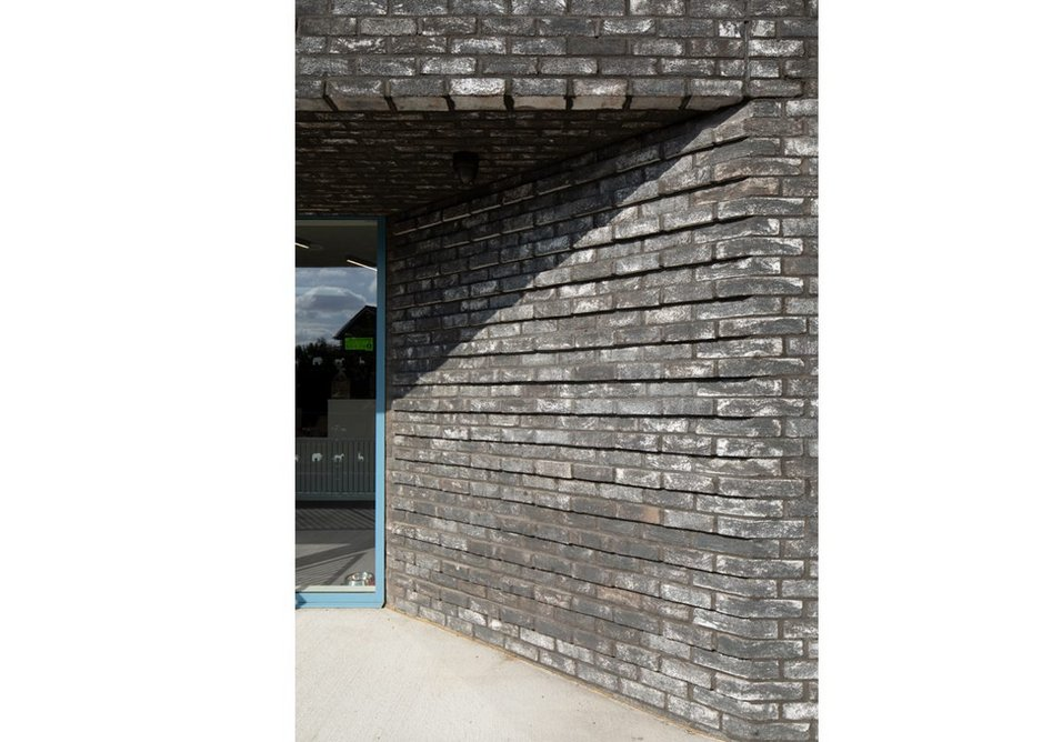 Brick detailing at the entrance evokes the stratification of the chalk caves below.