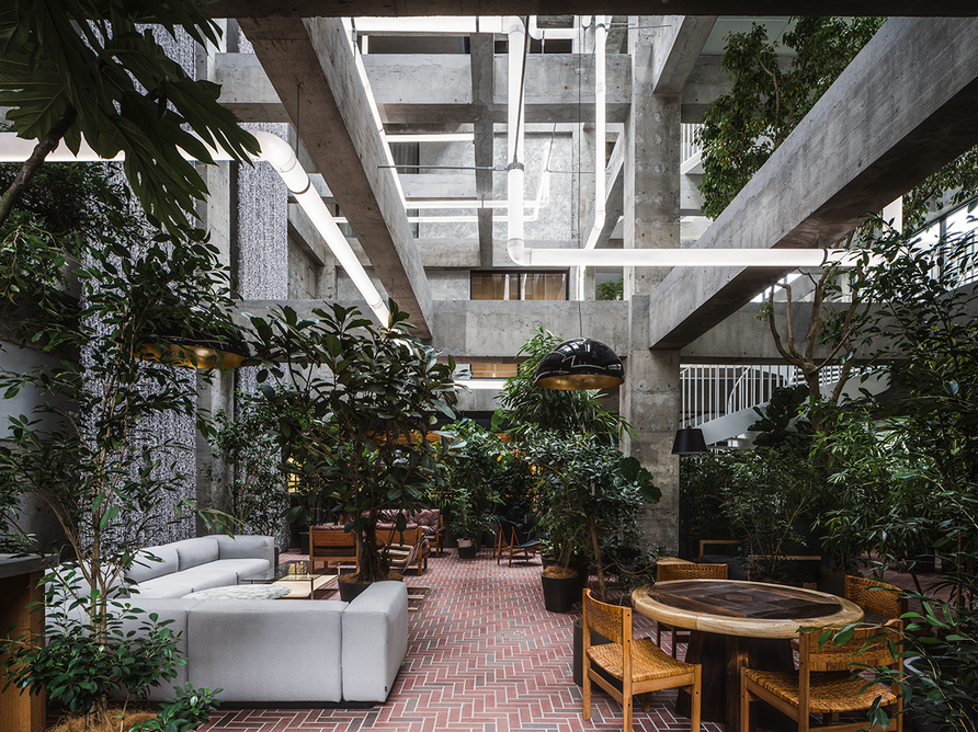 """The Lounge – designed by Fujimoto as a """"living room for the city"""" – has an excavated concrete interior, with cascading green plants, contemporary design classics and red brick herringbone floors, hinting at Maebashi's silk warehouse heritage."""