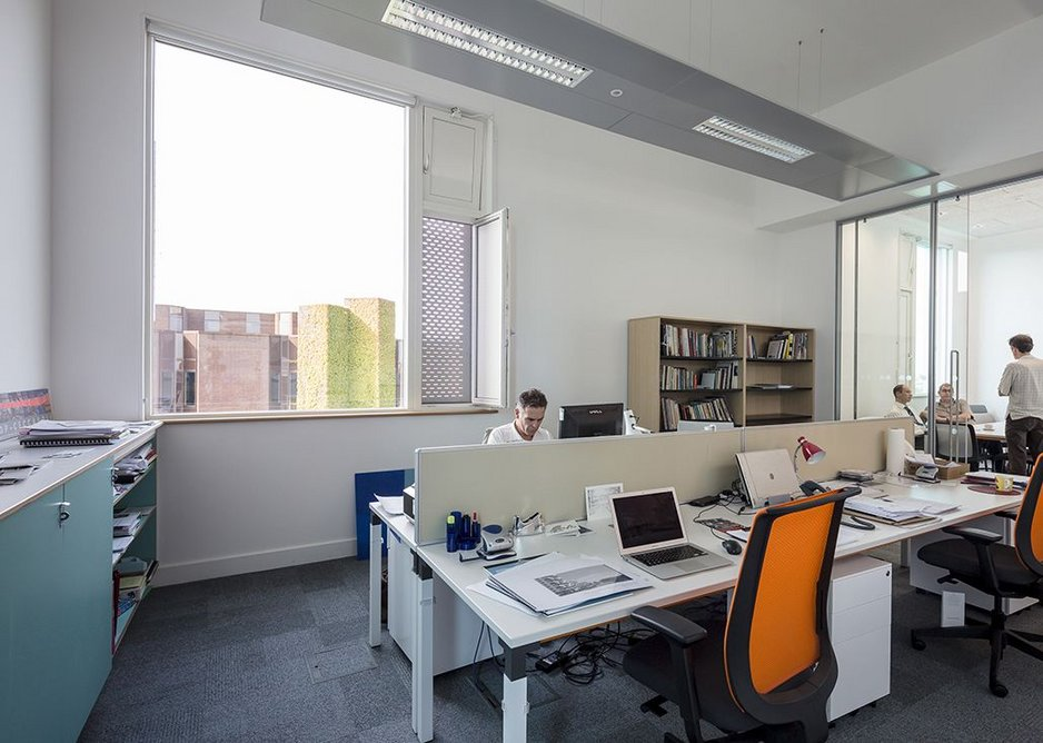 Lofty office spaces on the top floor. The splayed reveals of the tall windows act as night vents