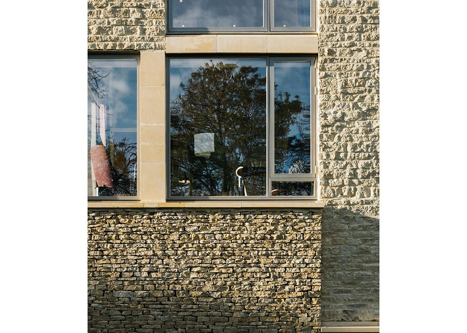 Limestone is laid like a boundary wall and then taken onto the front of the building with its more refined ashlar columns and oversized chimney to a shared residents snug.