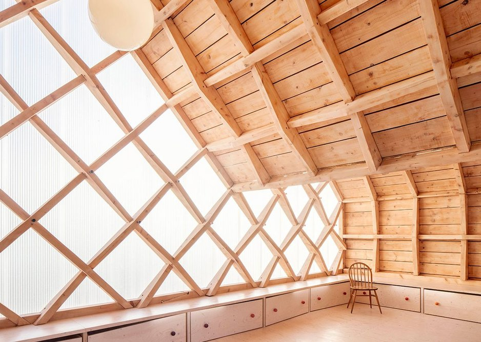 The expressed timber reciprocal frame of St. John's School Music Pavilion designed by Clementine Blakemore Architects at Lacey Green, Buckinghamshire. As part of the second phase of the project, the gable ends were clad in polycarbonate panels, with new storage created below.