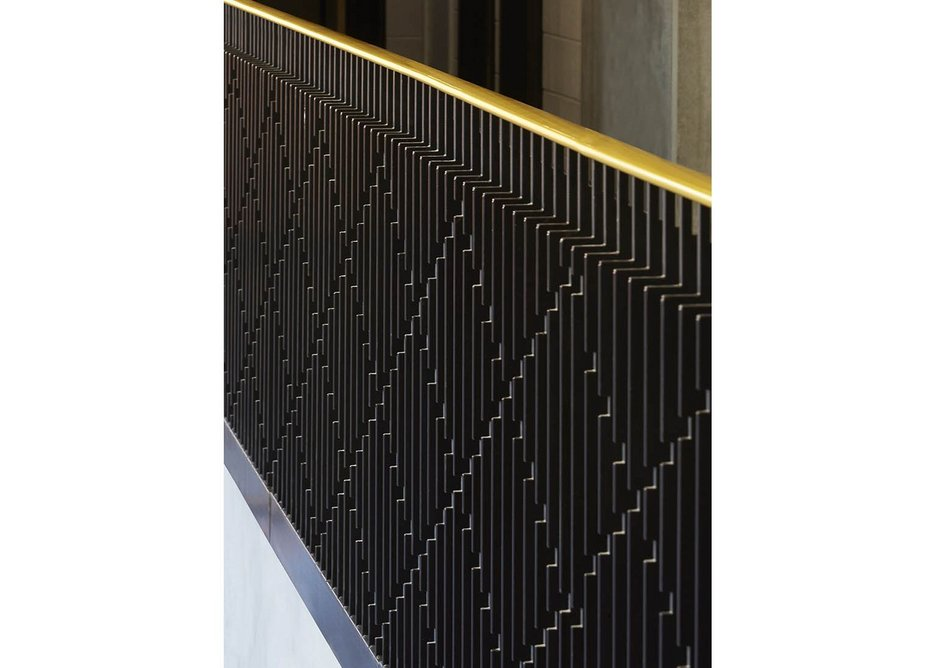 Laser cut nicks create a diagrid on the metal balusters, topped with yellow