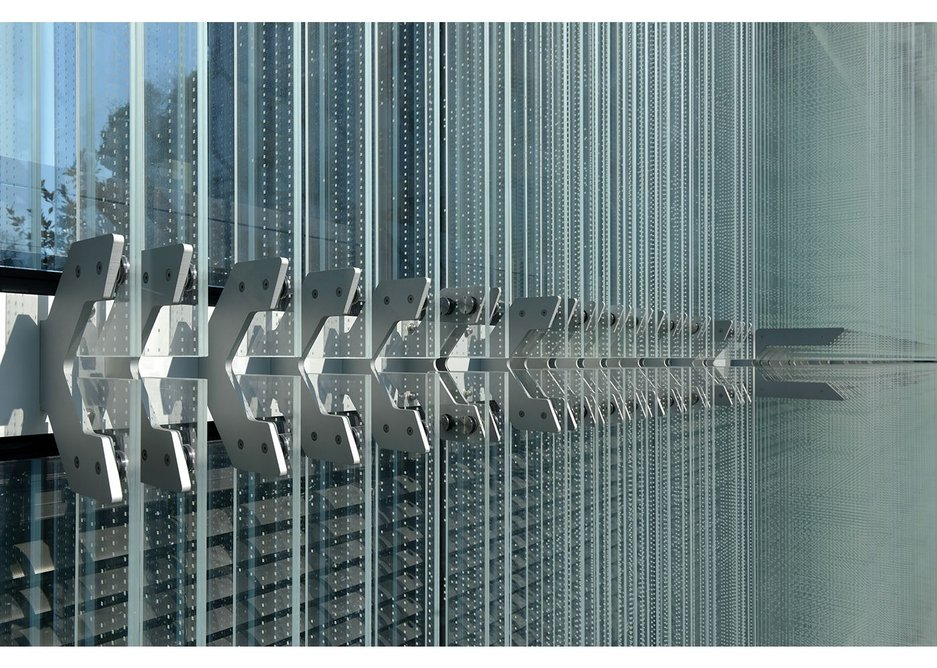 Aluminium clamps fixed at storey height  to the aluminium cladding framework hold the glass blades in place.