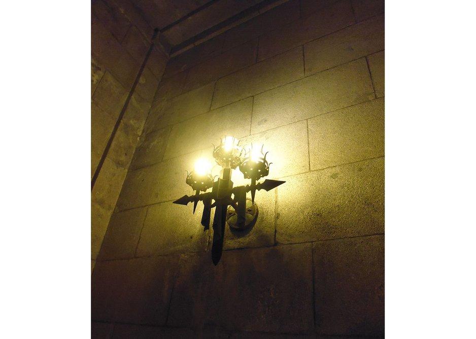 Side chapel sconces cast a vampish light and reference Falangist 'arrow' symbology.