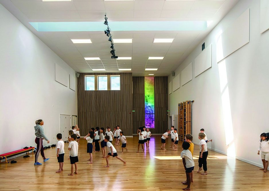 A transfer structure enables a column-free sports hall within the two-storey communal component of the radial school.