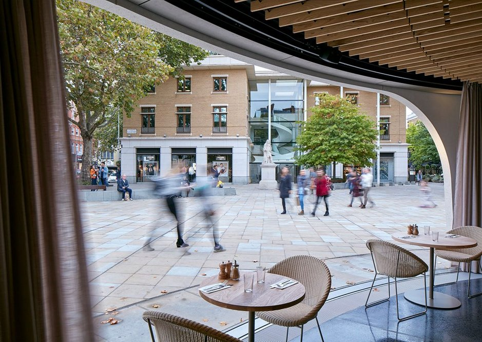 With the glass walls fully retracted into the floor, the pavilion meets the square.
