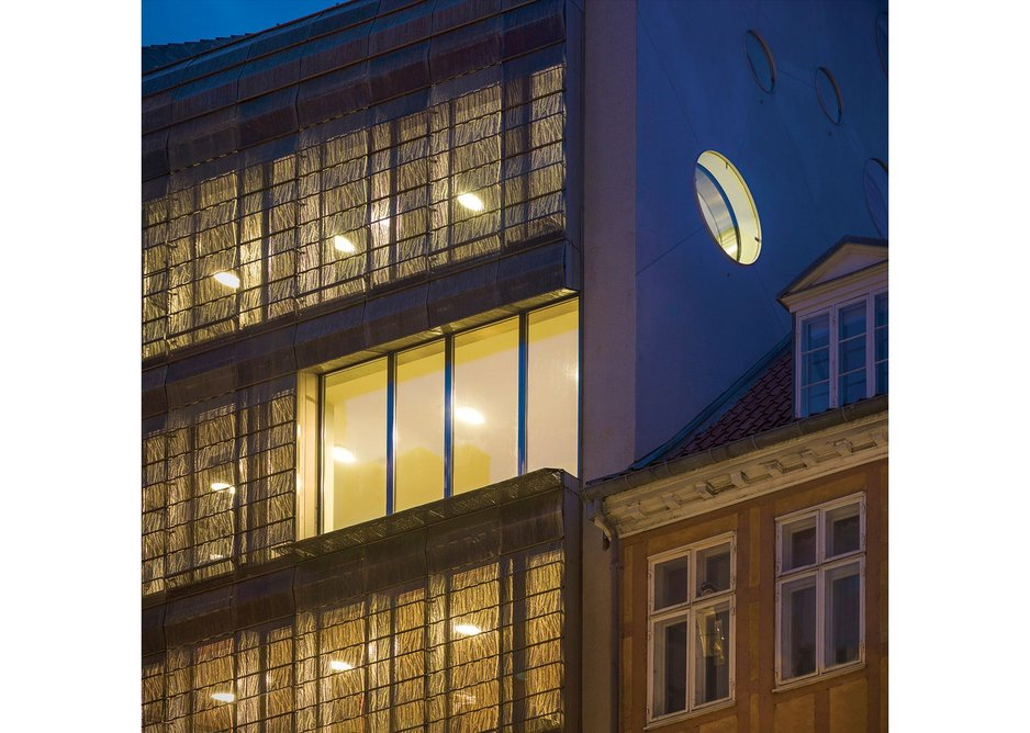Internal downlighters shine through the patterned brass at night, giving the building a golden glow.